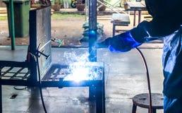 Pessoa de funcionamento sobre a máquina de soldadura de aço do soldador imagens de stock royalty free