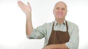 A pessoa de sorriso com avental faz olá! a sinal gestos de mão da saudação fotos de stock