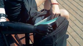 A pessoa deficiente com uma prótese toma seu portátil, sentando-se em um banco vídeos de arquivo