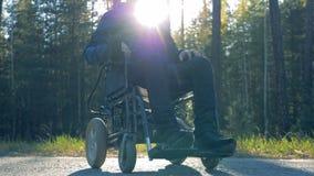 A pessoa deficiente está sentando-se em uma cadeira de rodas posta fora vídeos de arquivo