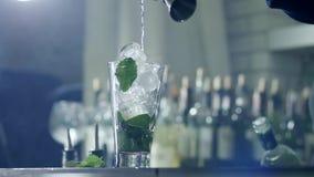 A pessoa derrama o álcool da garrafa e adiciona-o no vidro com gelo e hortelã no fumo fácil em fundo unfocused filme