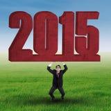 Pessoa do negócio com número 2015 no campo Fotografia de Stock Royalty Free