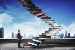 A pessoa do negócio intensifica o livro de voo que olha como a escada Imagem de Stock Royalty Free