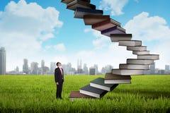 A pessoa do negócio intensifica o livro de voo que olha como a escada Imagens de Stock Royalty Free