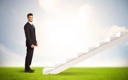 Pessoa do negócio que escala acima na escadaria branca na natureza Imagens de Stock