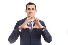 Pessoa do negócio que faz a forma da lareira com os dedos como o conceito do amor foto de stock royalty free