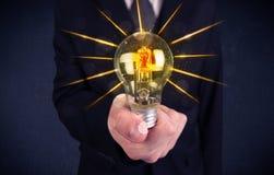 Pessoa do negócio que guarda uma ampola elétrica Fotos de Stock Royalty Free