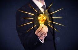 Pessoa do negócio que guarda uma ampola elétrica Imagem de Stock Royalty Free