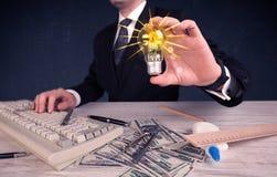 Pessoa do negócio que guarda uma ampola elétrica Fotografia de Stock Royalty Free