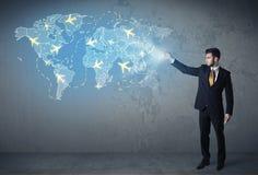 Pessoa do negócio que mostra o mapa digital com planos em todo o mundo Fotos de Stock Royalty Free