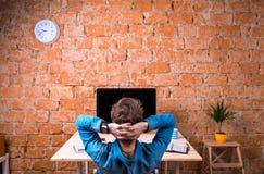 Pessoa do negócio que senta-se na mesa de escritório que veste o relógio esperto imagens de stock royalty free