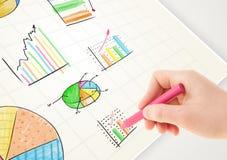Pessoa do negócio que tira gráficos e ícones coloridos no papel Imagens de Stock