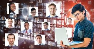 Pessoa do negócio que usa o portátil contra retratos Imagens de Stock Royalty Free