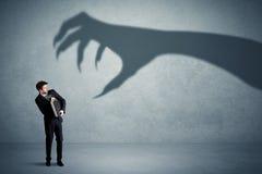 Pessoa do negócio receosa de um conceito grande da sombra da garra do monstro Fotos de Stock Royalty Free