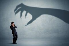 Pessoa do negócio receosa de um conceito grande da sombra da garra do monstro Fotografia de Stock Royalty Free