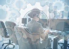 Pessoa do serviço ao cliente em computadores atrás da folha de prova do gráfico da engrenagem imagem de stock royalty free