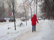 Pessoa do vermelho em um revestimento para baixo, rua coberto de neve Foto de Stock