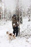 Pessoa e seu jogo do cão com neve imagens de stock