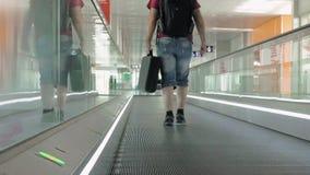A pessoa está andando em caminho movente no aeroporto video estoque