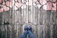 A pessoa está no assoalho de madeira com corações Imagem de Stock Royalty Free