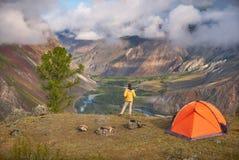 A pessoa está perto do acampamento e do olhar no vale da vista Imagens de Stock Royalty Free