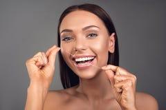 Pessoa fêmea alegre que usa o fio dental imagens de stock royalty free