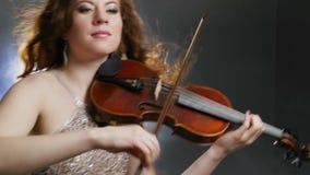 A pessoa fêmea joga emocionalmente na sociedade filarmônica do fim do violino acima dentro no fundo da luz e do fumo brilhantes vídeos de arquivo
