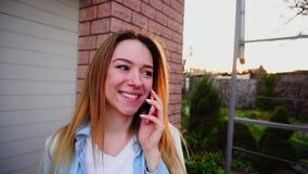 Pessoa fêmea nova que fala pelo smartphone perto da garagem no movimento lento filme