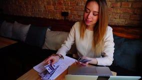 Pessoa fêmea que conta o dinheiro no café e que trabalha com portátil e originais filme