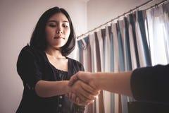 Pessoa fêmea que olha o aperto de mão com cara confusa Fotografia de Stock Royalty Free