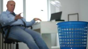 Pessoa furada que senta-se na cadeira do escritório e no papel amarrotado de jogo na cesta do lixo video estoque