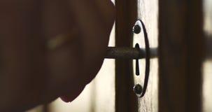 A pessoa gerencie ? m?o a chave velha no buraco da fechadura do arm?rio de madeira antigo vídeos de arquivo