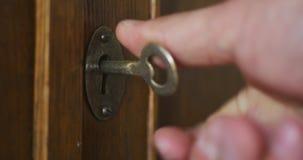 A pessoa gerencie ? m?o a chave velha no buraco da fechadura do arm?rio de madeira antigo filme