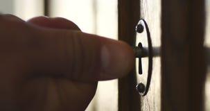 A pessoa gerencie ? m?o a chave velha no buraco da fechadura do arm?rio de madeira antigo video estoque