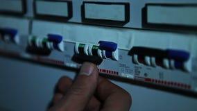 A pessoa gerencie o interruptor do painel filme