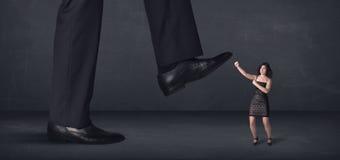 Pessoa gigante que pisa em um conceito pequeno da mulher de negócios Fotografia de Stock