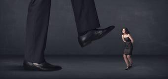 Pessoa gigante que pisa em um conceito pequeno da mulher de negócios Imagem de Stock