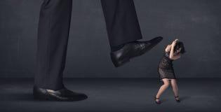 Pessoa gigante que pisa em um conceito pequeno da mulher de negócios Imagens de Stock Royalty Free