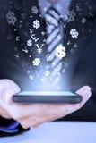 A pessoa guarda o smartphone com símbolos de moeda Foto de Stock Royalty Free