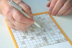 Pessoa idosa que faz o enigma de palavras cruzadas Fotografia de Stock Royalty Free