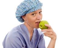 Pessoa médica da enfermeira que come a maçã do smith de avó fotografia de stock