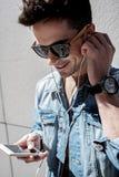 Pessoa masculina de sorriso interessada que usa o telefone imagens de stock