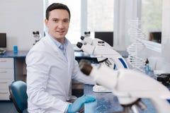 Pessoa masculina deleitada positiva que trabalha no laboratório Fotos de Stock