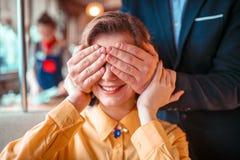 A pessoa masculina fecha as mãos dos olhos à mulher bonita fotografia de stock royalty free