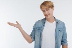 Pessoa masculina positiva que põe a mão como se demonstrando algo Imagens de Stock
