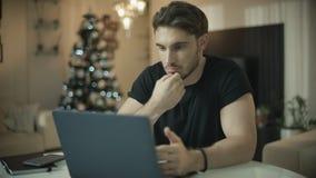 Pessoa masculina que usa o portátil na casa no feriado do Natal Homem que trabalha no computador video estoque