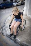 Pessoa na cadeira de rodas que tenta cruzar a estrada Imagens de Stock