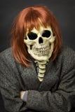 Pessoa na máscara da morte e da peruca vermelha Fotografia de Stock Royalty Free