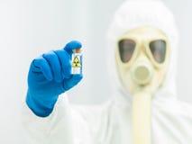 Pessoa no terno protetor que guarda a amostra do isótopo Fotos de Stock
