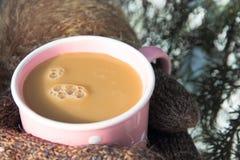 Pessoa nos mitenes que guardam um copo do cappuccino Fotografia de Stock Royalty Free